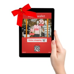 female hand holding a tablet with red gift bow and mobile wallet onlain shopping on the screen