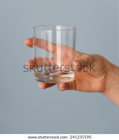 Female hand holding an empty glass.