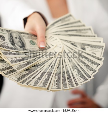 Female hand holding and sharing stack of 100 dollar banknotes