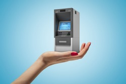 Female hand holding ATM machine on blue background. Banking and finance. Business success. Management and income.