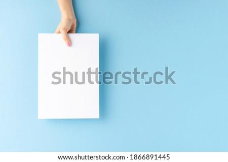 Female hand holding blank white paper sheet on blue background. Mock up Stockfoto ©