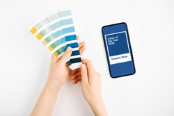 Female hand holding color swatches and  smartphone with color of the year 2020 - Classic Blue. Color trend palette.