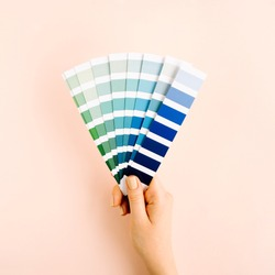Female hand holding color swatches. Color trend palette. Flat lay, top view.