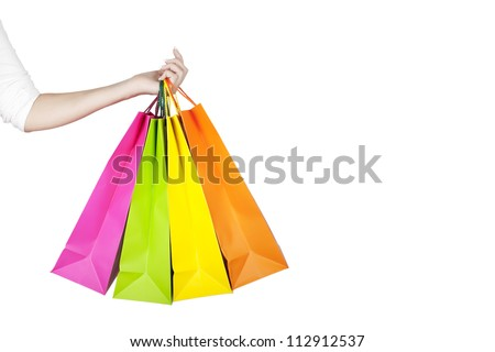 Female hand holding colorful shopping bags