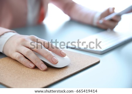 Female hand holding computer mouse on pad #665419414