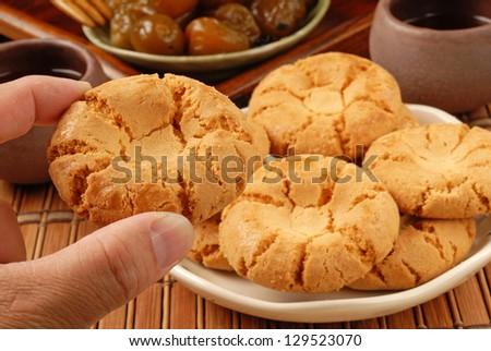 Female hand holding crisp walnut cookie