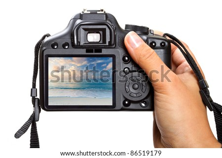 Female hand holding DSLR camera isolated on white
