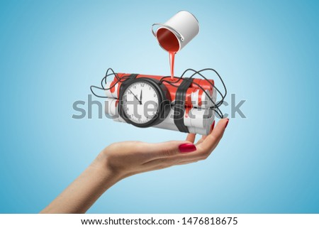 Female hand holding dynamite stick time bomb with red paint bucket turned upside down above it on blue background. Digital art. Objects and materials. Explosive materials.