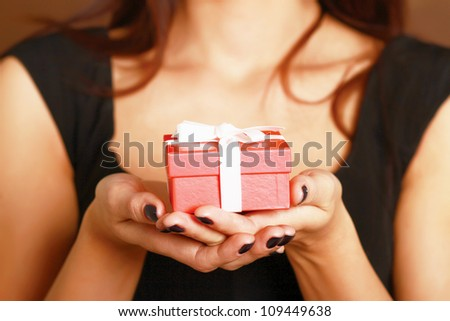 Female hand holding gift box isolated on red background