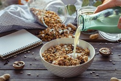 Female hand holding glass bottle pouring milk in cereal granola flakes bowl with nuts seeds raisins on brown wooden table background, healthy breakfast lifestyle concept, home muesli food oat meal