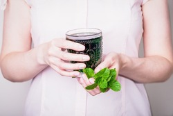 Female hand holding glass of green chlorophyll drink with fresh mint leaves
