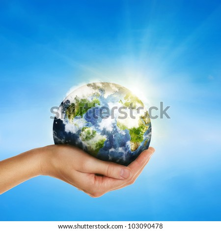 female hand holding globe over blue sky - environment protection and travel concept -Elements of this image furnished by NASA