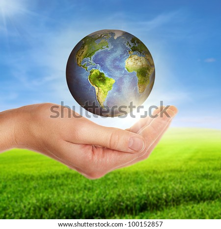 female hand holding globe over green field and cloudy blue sky