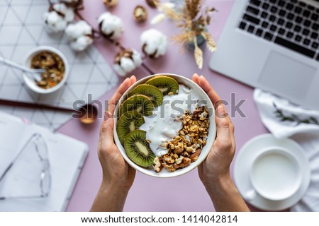 Female hand holding healthy breakfast bowl over work table background concept enjoy detox morning meal with laptop milk, woman eat natural granola nutrition detox food in home office, top view