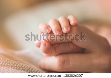 Female hand holding her newborn baby's hand. Mom with her child. Maternity, family, birth concept. Copy space for your text. Stock fotó ©