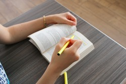 Female hand holding highlighter pen, highlighting  marking important texts in book on wooden table background.