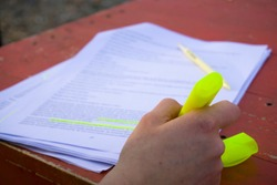 Female hand holding highlighter pen, highlighting / marking important texts in study sheets on table background.