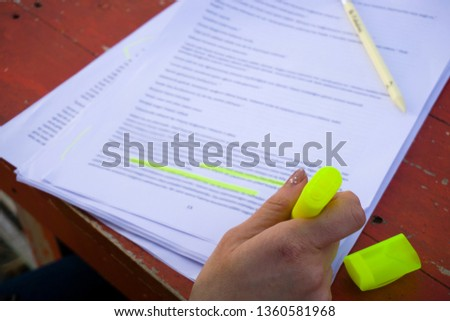 Female hand holding highlighter pen, highlighting / marking texts in study sheets on table background.