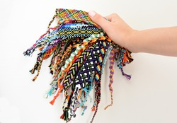 Female hand holding many woven multi-colored DIY friendship bracelets handmade of embroidery thread with knots on white background.