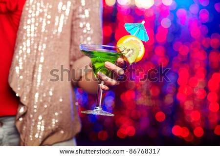 Female hand holding martini glass with cocktail
