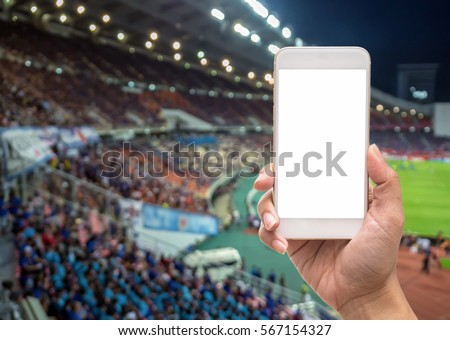 Female hand holding mobile smart phone touch screen on Abstract blurred photo crowd of spectators on a stadium with a football match, sport background concept