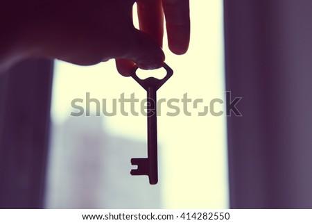 female hand holding old key on...