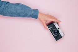 Female hand holding old retro photo camera on pink background with copy space for text. Trendy vintage photography, online photography school concept. Selective focus