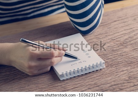 Female hand holding pen writing business plan to do list on wood table in vintage color effect, task priority and work or day to day organize.