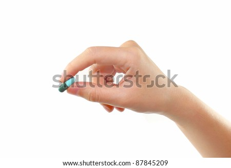 female hand holding pill isolated
