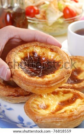 Female hand holding portuguese  egg  tart - stock photo