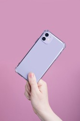 Female hand holding purple iPhone 11 in transparent cover isolated on a pink background. Clear phone case mock up back view