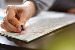 Female hand holding pushpin showing the location of a destination point on a map. Travel destination, pin on the map. Selective focus. Blue pushpin, map on table. High quality photo