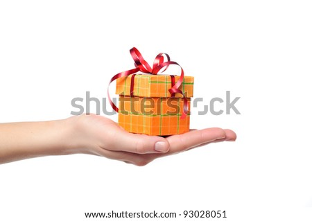 female hand holding red and yellow gift box with a bow isolated on white background