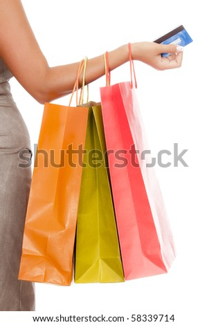 Female hand holding shopping bags and credit card