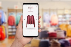Female hand holding smartphone and shopping online, blurred clothing store in background. Online shopping concept