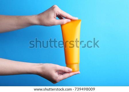 Female hand holding sunscreen cream on blue background #739498009