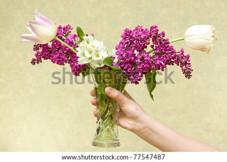 Female hand holding vase with various flowers.