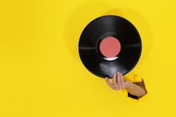 Female hand holding Vinyl Record through torn hole in yellow paper wall. Minimalistic retro concept