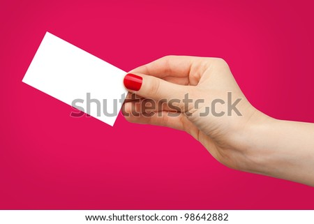Female hand holding white business card on red background.