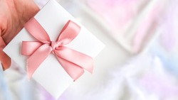 Female hand holding White gift box with pink ribbon on white silk texture background. Colorful bird feather. Holiday concept. Present for Valentines Birthday Mothers Womans day