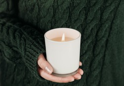 female hand holding white soy candle. teenager girl wearing green sweater and holding burning candle. holidays concept. spiritual experience and inner peace. selective focus