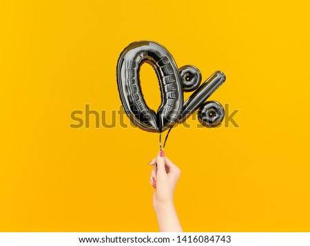 Female hand holding Zero percent symbol. 0 % banner black flying foil balloons on yellow. 3d rendering.