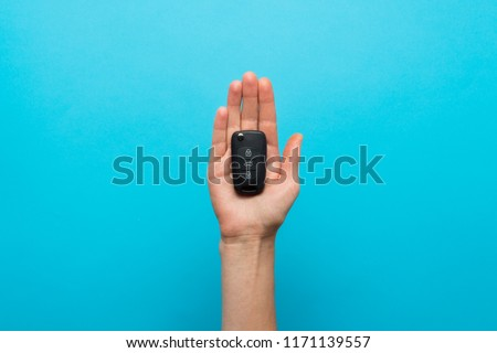 Female hand holds a car key in the palm on a blue background. Co
