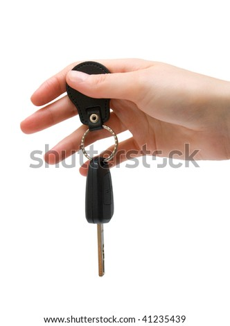 Female hand holds a car key. Isolated.