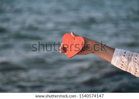 Female hand holds a red decorative heart on a background of waves. The concept of Valentine's day, honeymoon and honeymoon at sea #1540574147