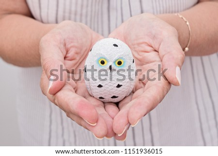 Stock Photo Female hand holds ceramic small owl in palm. Christmas time and new year concept