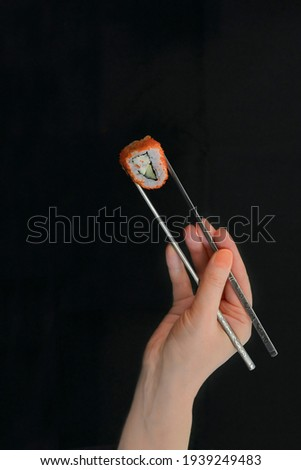 Female hand holds chopsticks and sushi roll on black background  Foto stock ©