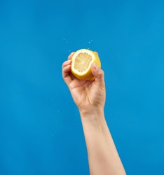 female hand holds half a yellow lemon and squeezes it on a blue background, splashes fly to the sides