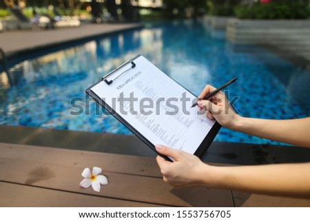female hand holds out pen, fills out visa application form in United States. Sunny portrait on pool background And sunlight. concept of traveling to new countries.