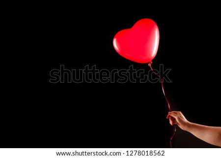 Female hand holds red rubber inflatable heart shape balloon. Love, relationship, valentines day and birthday celebration concept. Studio shot on an abstract blurred background with blank copy space #1278018562